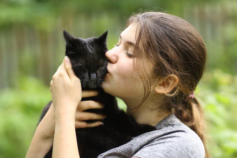 少女拥抱黑猫的夏日艳照 库存照片