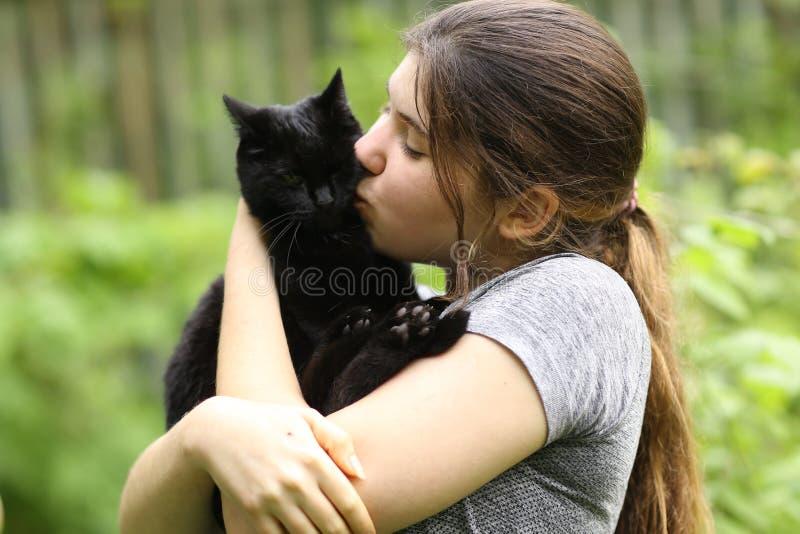 少女拥抱黑猫的夏日艳照 免版税库存图片