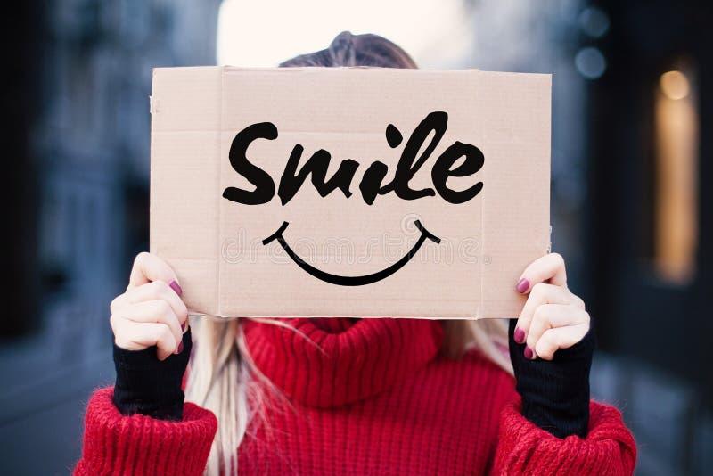 少女拿着与微笑的一个标志 愉快和微笑的概念 免版税图库摄影
