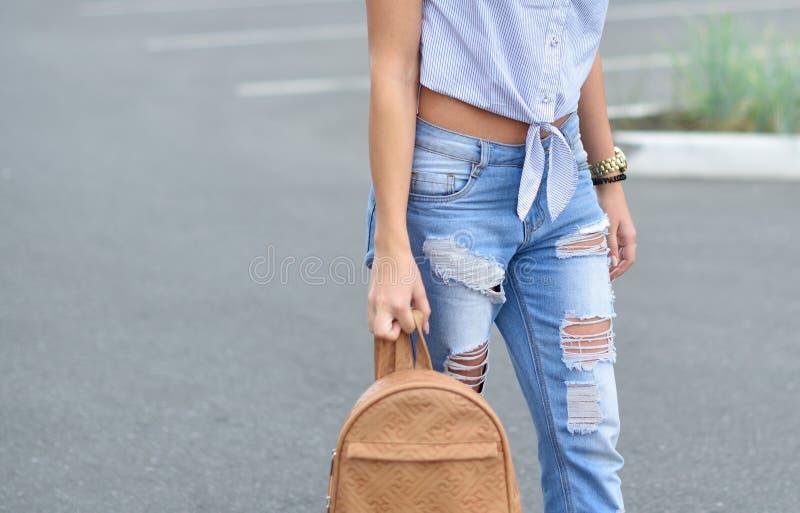 少女步行沿着向下有一个米黄背包的街道在被撕毁的蓝色牛仔裤 在青少年的腿的时兴的被剥去的蓝色牛仔裤 免版税图库摄影
