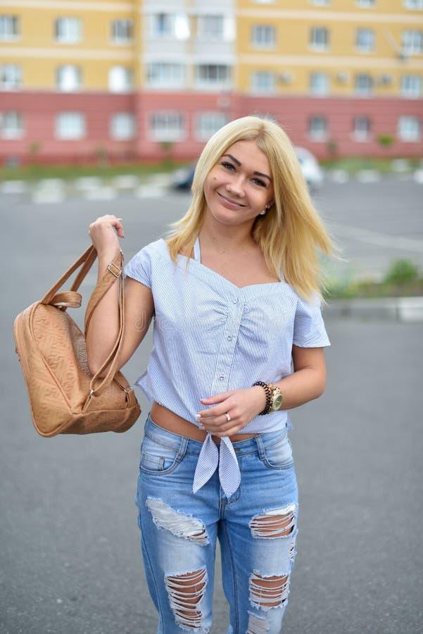 少女步行沿着向下有一个米黄背包的街道在被撕毁的蓝色牛仔裤 在青少年的腿的时兴的被剥去的蓝色牛仔裤 免版税库存图片