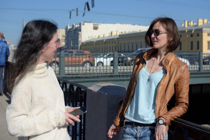 少女游人有中止在桥梁在圣彼德堡,俄罗斯并且谈论进一步观光 免版税库存照片