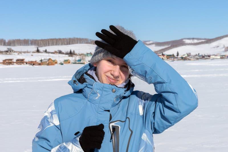 少女滑雪者由从太阳的一只手在一个雪白冻湖阻拦,站立以村庄为背景 免版税库存图片