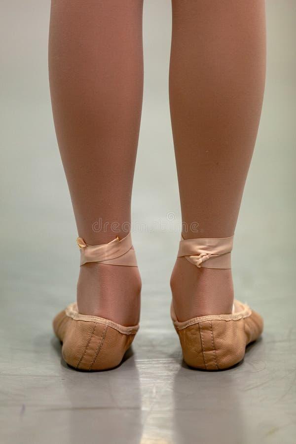 少女特写镜头前pointe在芭蕾与滚动的脚腕的学校课程-在不正确芭蕾第一个第1个位置 库存照片
