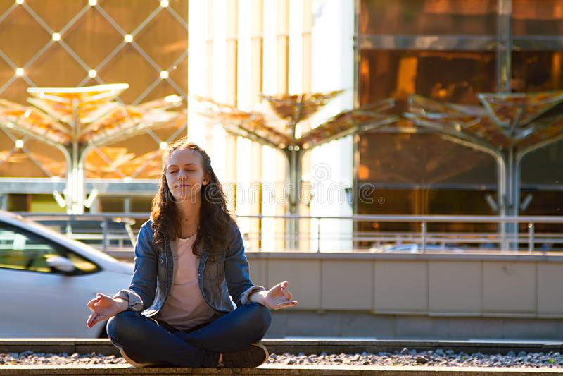 少女瑜伽和在莲花坐思考在一个大城市 免版税库存照片
