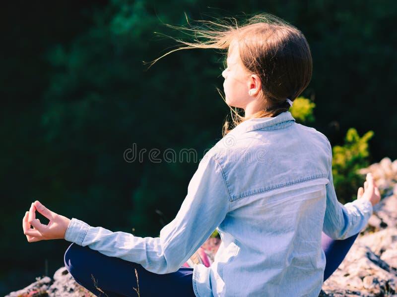 少女瑜伽思考在日落坐在山的一个岩石在莲花坐 免版税库存照片