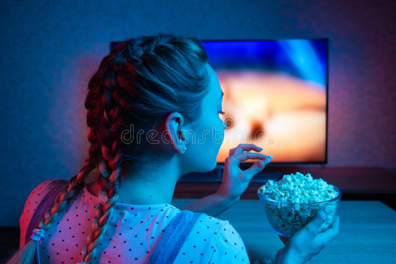 少女电影和吃玉米花与一个碗在电视的背景 颜色明亮的照明设备,蓝色和红色 库存照片