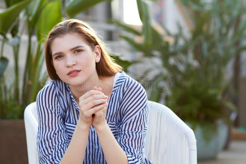 少女画象在白色扶手椅子坐反对被弄脏的balckground 库存图片