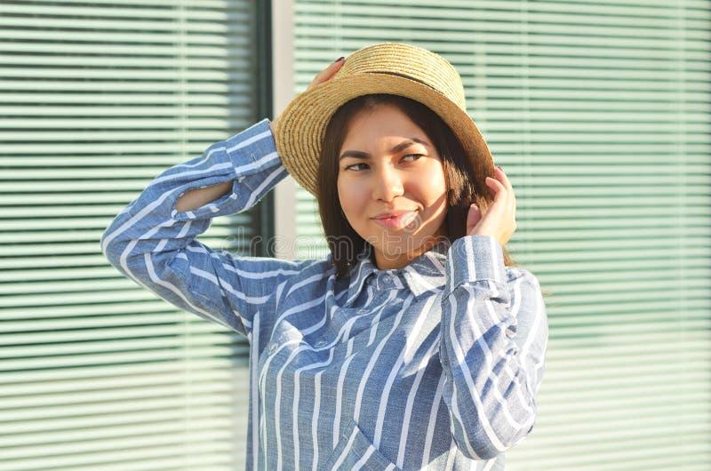 少女的画象在帽子的墙壁附近站立,并且她在蓝色镶边衬衣打扮 免版税库存照片