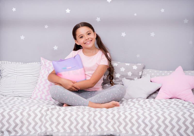 少女秘密 女孩孩子坐与袋子的床或化妆用品在她的卧室请求 孩子准备上床 宜人的时间 库存照片