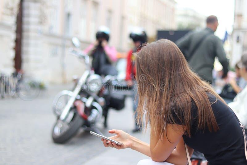 少女调查举行的智能手机 妇女在古城的中心坐一条长凳反对moto 免版税库存图片