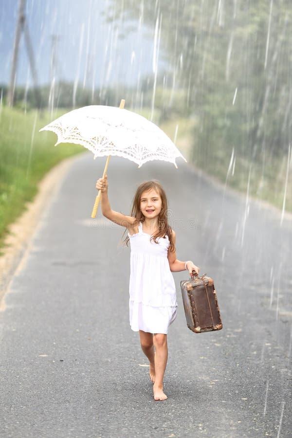 少女走与手提箱和伞在雨中 库存图片