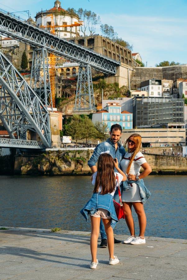 少女takesk夫妇的图片在Ribeira在Dom路易斯一世桥梁,波尔图,葡萄牙附近的杜罗河河岸中 免版税库存照片