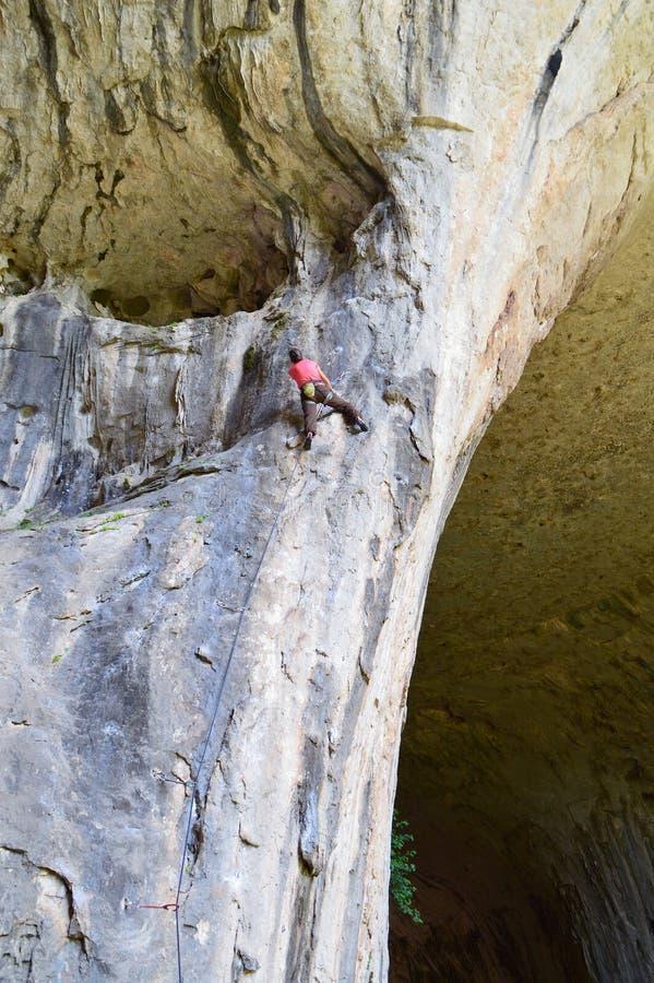 少妇上升在洞的攀岩运动员 库存照片