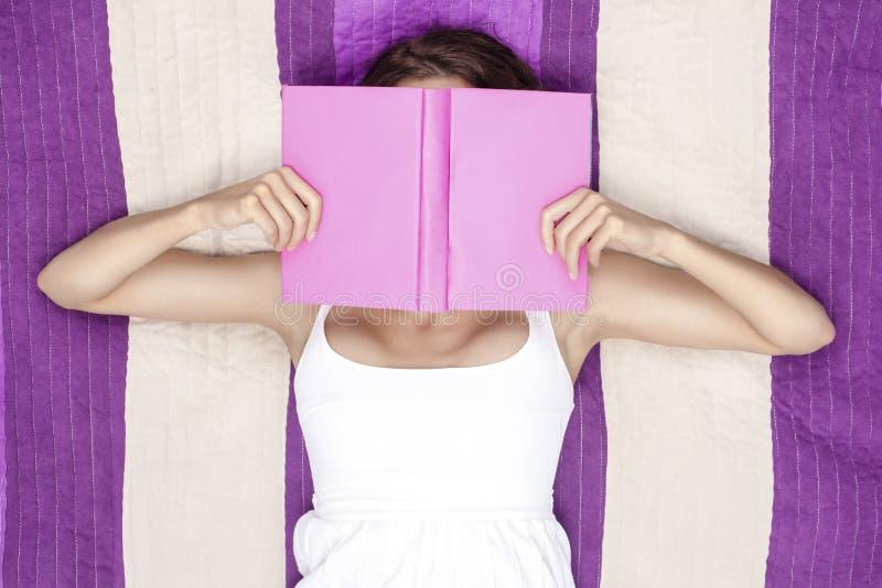 少妇与书的覆盖物面孔,当说谎在野餐毯子时 免版税库存照片