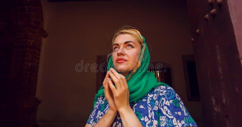 少妇为祈祷一起折叠了她的手在历史教会里面 免版税库存照片