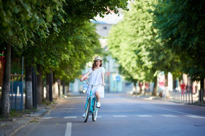 少妇乘坐在路在减速火箭的自行车,夏日 库存照片