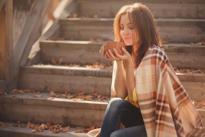 少妇休息和饮用的茶在秋天庭院里坐步,包裹在一条羊毛格子花呢披肩毯子 图库摄影