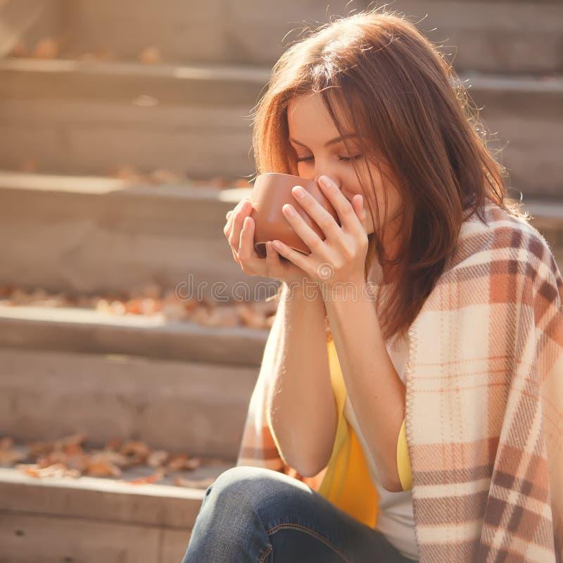 少妇休息和饮用的茶在秋天庭院里坐步,包裹在一条羊毛格子花呢披肩毯子 库存图片