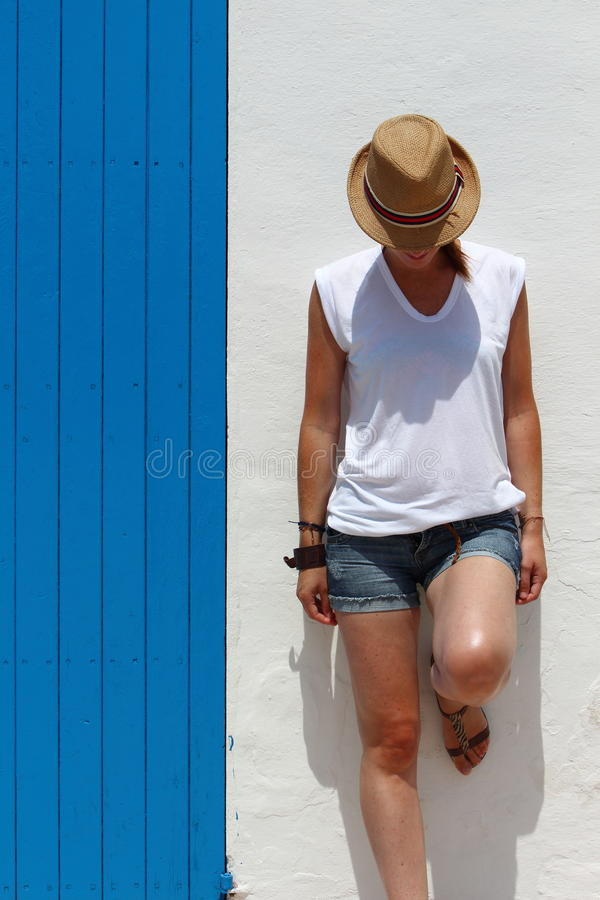 少妇休息接近在一个典型的村庄大厦的一个蓝色木门的,福门特拉岛,巴利阿里群岛,西班牙 免版税库存照片
