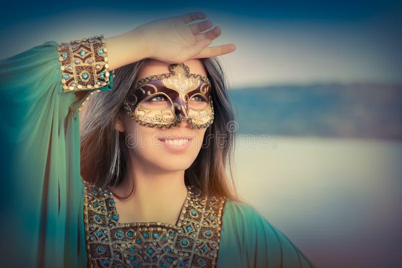 少妇佩带的面具和东方礼服 免版税图库摄影