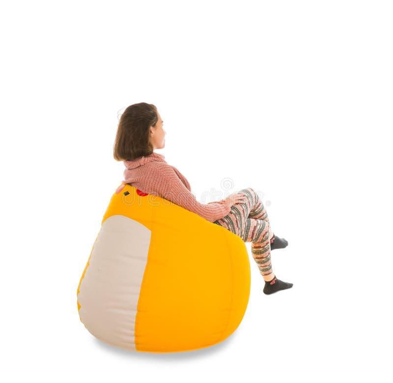 少妇侧视图坐黄色装豆子小布袋椅子孤立 免版税库存照片