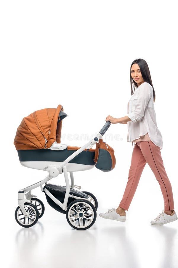 少妇侧视图有婴儿婴孩的婴儿车的 免版税库存照片