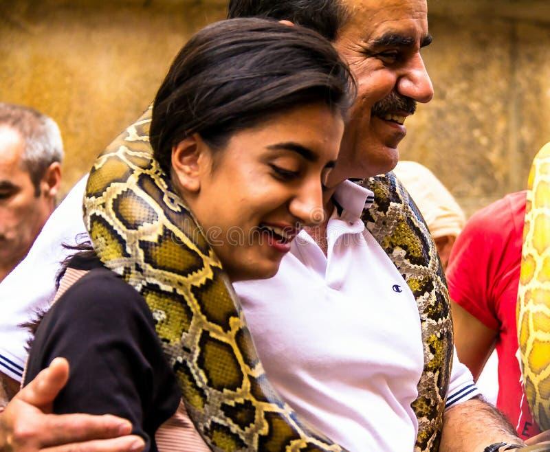 少妇做与一个巨大的黄色蟒蛇蛇缩窄器的ande人照片在脖子,老镇,布拉格,捷克 免版税图库摄影