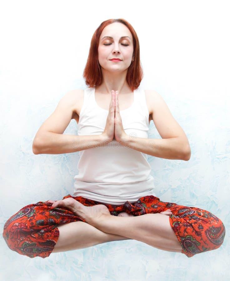 少妇做瑜伽户内 免版税库存图片
