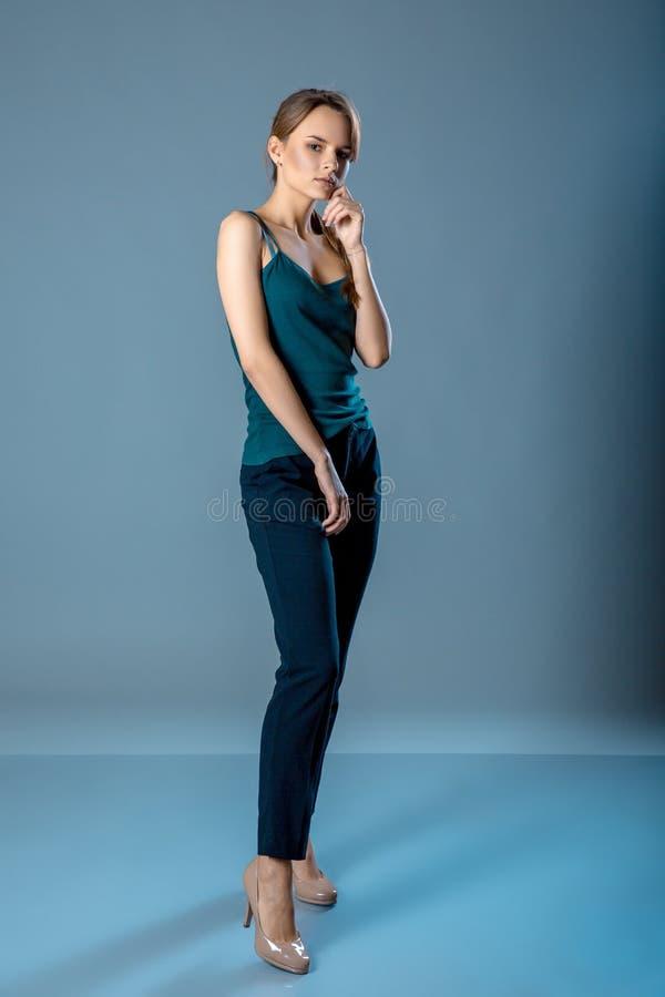少妇全长画象深绿站立在蓝灰色背景的衬衣和黑暗的裤子的 免版税库存图片