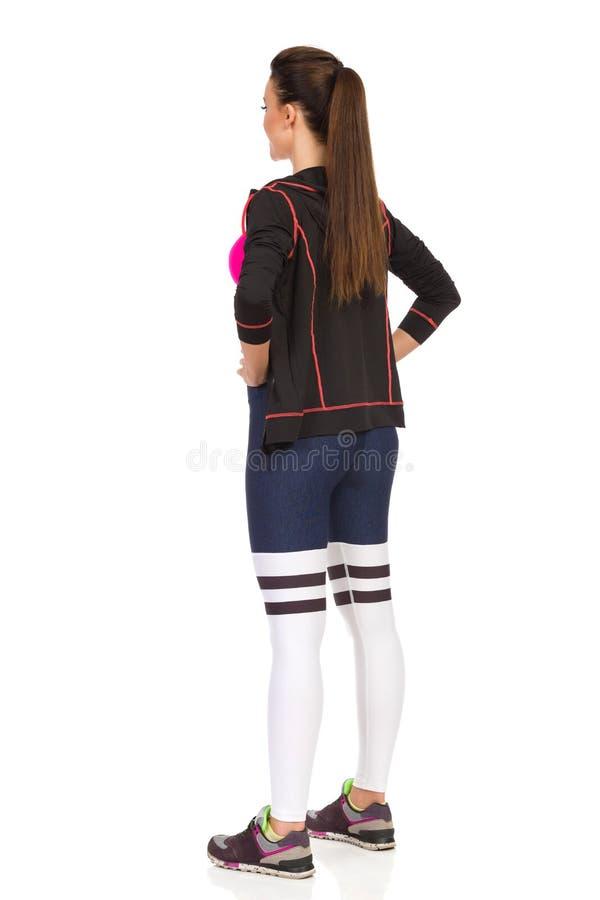 少妇分开站立腿在健身衣裳 后面视图 免版税库存图片