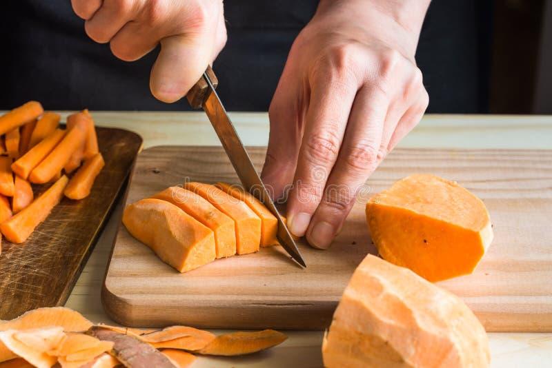 少妇切口用刀子白薯到楔子,在木桌上的果皮里,切了红萝卜 免版税库存图片