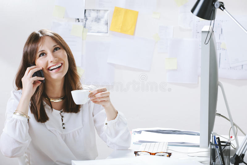 少妇创造性的设计师谈话与电话,当喝咖啡时 库存照片