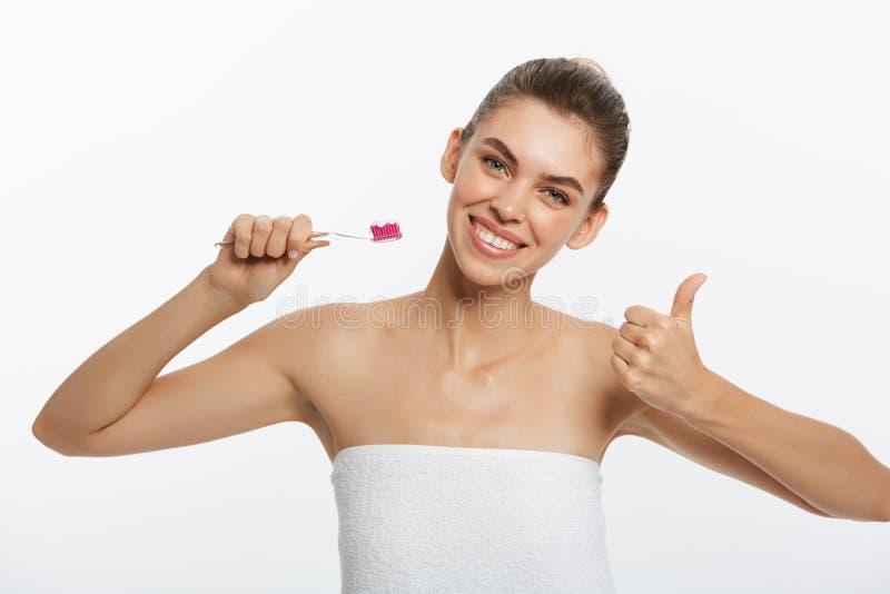 少妇刷子清理牙 女孩拿着有牙膏的牙刷对显示赞许手势的此 口头 库存图片