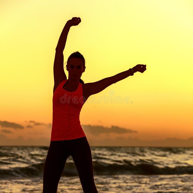 少妇剪影体育的在海岸锻炼适应 免版税库存图片