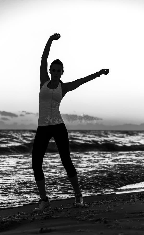 少妇剪影体育的在海岸锻炼适应 免版税库存照片