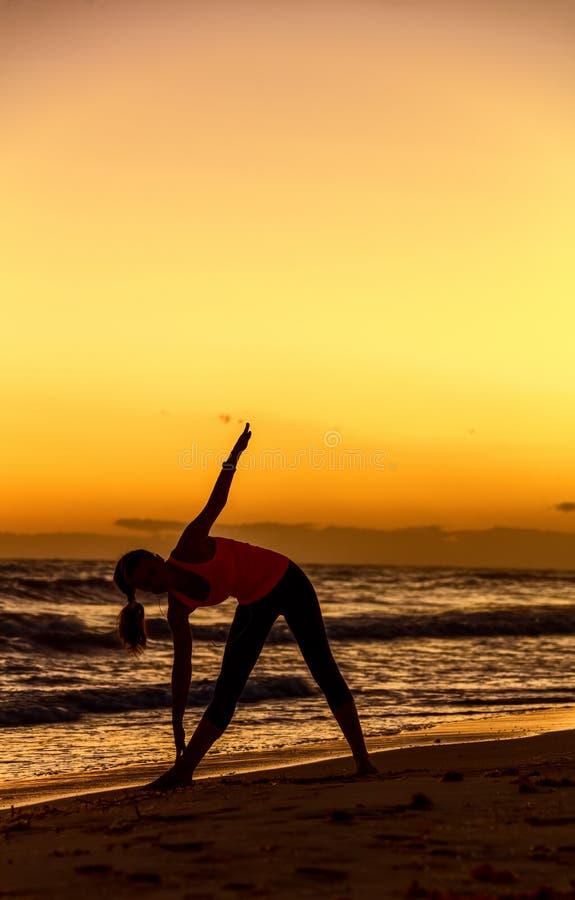 少妇剪影体育的在海滩锻炼适应 免版税库存图片