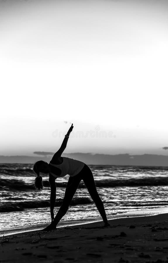 少妇剪影体育的在海滩锻炼适应 免版税库存照片