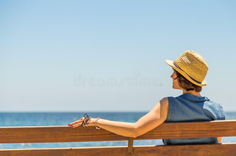 少妇单独坐在海前面的一条长凳 库存照片