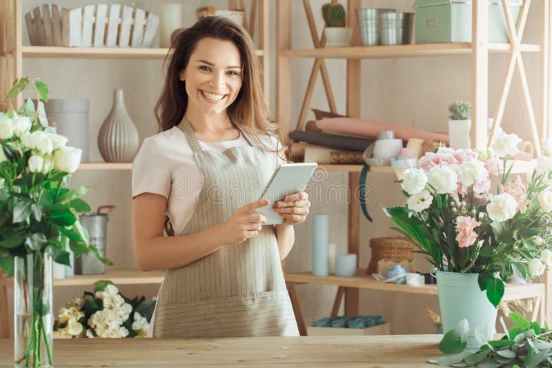 少妇卖花人职业与花一起使用 免版税库存照片