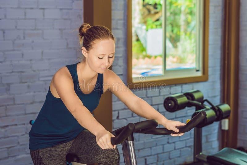 少妇参与自行车健身房 免版税库存图片