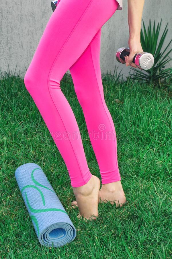 少妇向体育求助 演奏体育本质上与哑铃的女性腿 库存照片