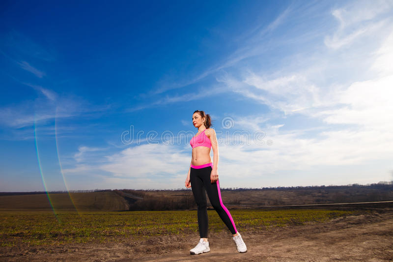 少妇向在蓝天背景的体育求助 库存照片