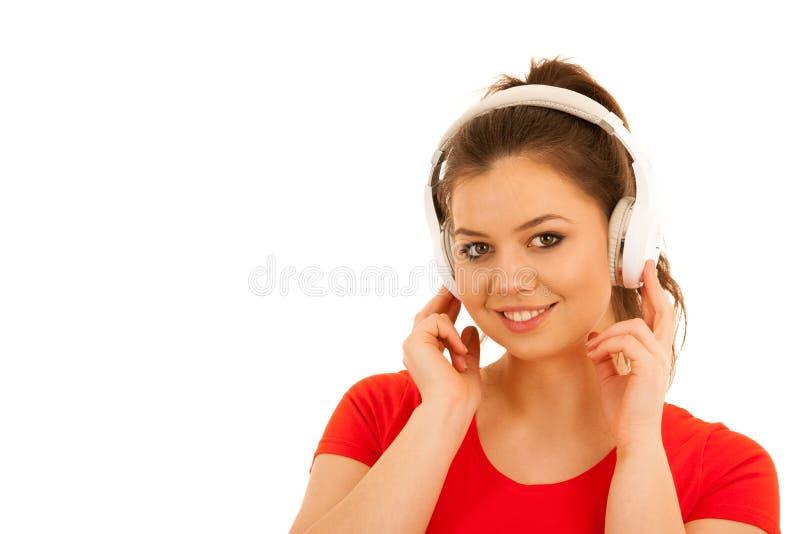 少妇听与耳机的音乐被隔绝在白色backg 库存照片