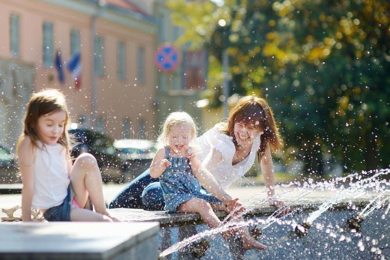 少妇和两个孩子由城市喷泉 免版税图库摄影