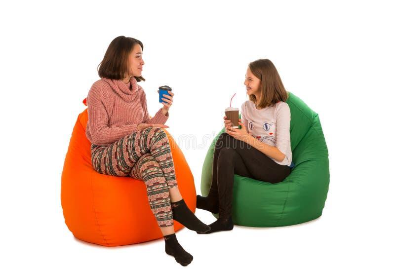 少妇和女孩坐装豆子小布袋椅子和饮用的co 免版税库存图片