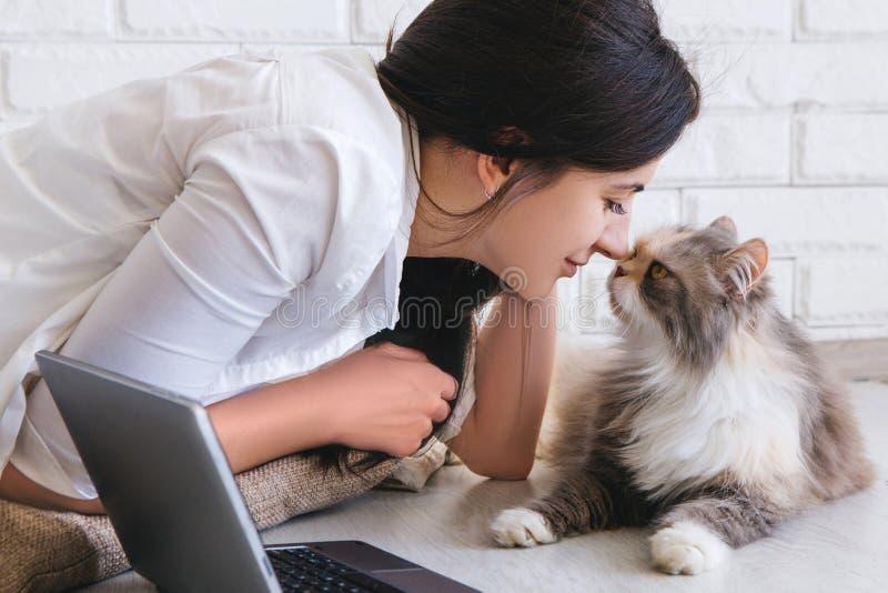 少妇和她可爱的猫摩擦鼻子 免版税图库摄影