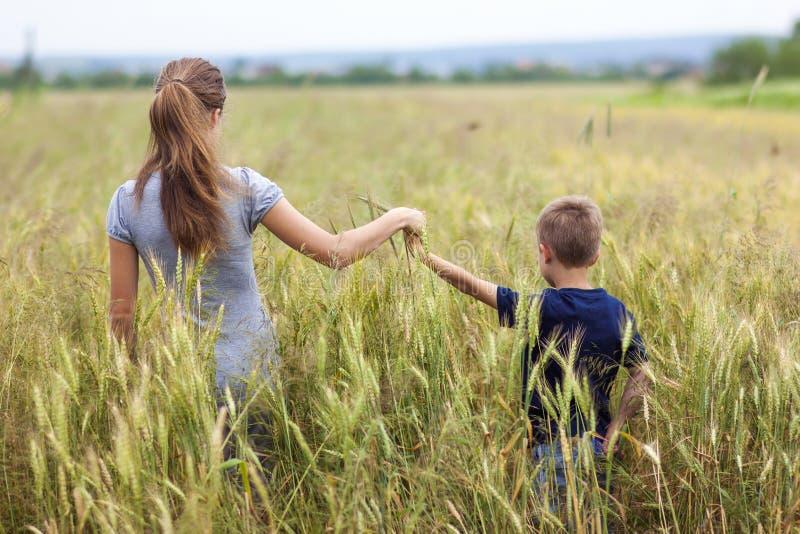 少妇和小男孩她的站立在麦田的儿子 单 图库摄影