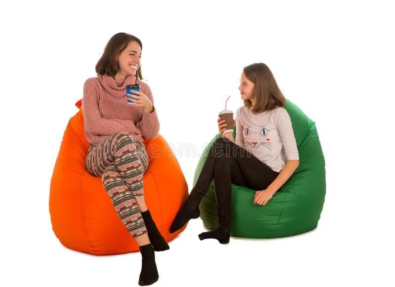 少妇和微笑的女孩坐装豆子小布袋椅子和饮料 图库摄影