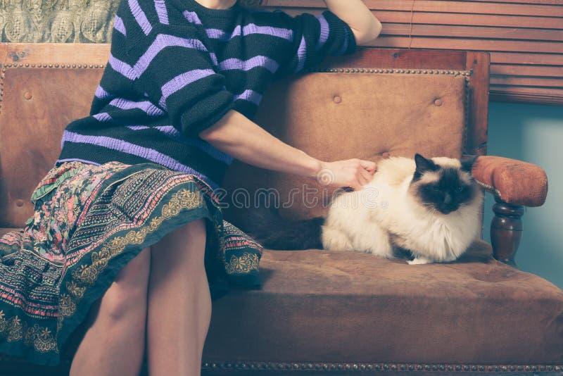 少妇和猫在沙发 免版税库存图片